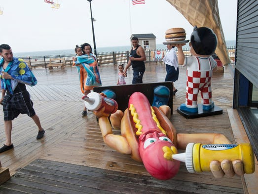 Seaside Heights visitors look perplexed as they pass a hot dog man statute left laying flat on the boardwalk to protect it from being damaged by the possible high winds as Hurriane Arthur passes by. People enjoy early July 4th morning before rains grew heavier as Hurricane Arthur rolled by heading towards New England. Photo taken July 4, 2014 in Seaside Heights. Peter Ackerman / Staff Photographer