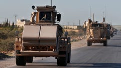A U.S. mine detector armored vehicle, leads a convoy