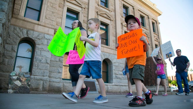 Andrea Radford (L-R), Domnick Redford and Donevin Sweeney carry signs during a protest of potential cuts to education outside the State Capitol in March.