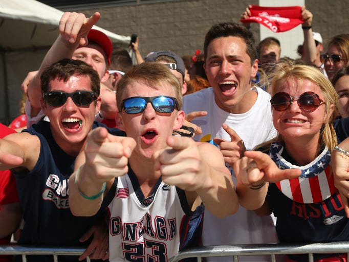 Gonzaga student Corey Johnson (center) cheers with
