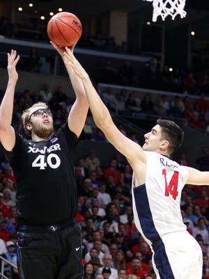 Xavier's Matt Stainbrook shoots over Arizona's Dusan Ristic during the first half Thursday in Los Angeles.