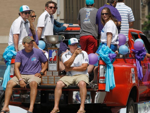Rochester Knighthawk players Sid Smith, bottom left, and Cody Jamieson, right, sit on the bumper alongside the NLL Championship trophy during the Knighthawks 2014 NLL Championship parade held June 10, 2014, in downtown Rochester.