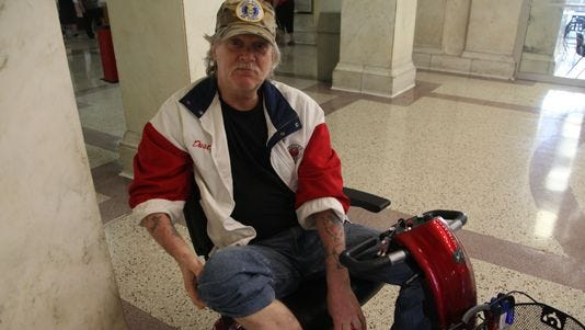 Dusty Donaldson shows his bedbug-related scars at the Polk County Courthouse. He says he expects to receive about $7,000 as part of a $2.45 million class-action settlement that was approved Wednesday.