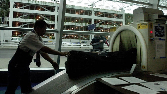 A worker sends baggage through a screening machine at Portland International Airport.