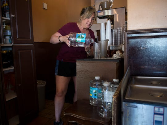 Claudine Williams, a server at Maria's Cafe, pours bottled water for customers Tuesday at the diner in Stuart. Because of a water pressure drop at Stuart's water-treatment facility on Palm Beach Road, the city ordered a precautionary boil water advisory for the city's 4,200 accounts, about 17,300 people.