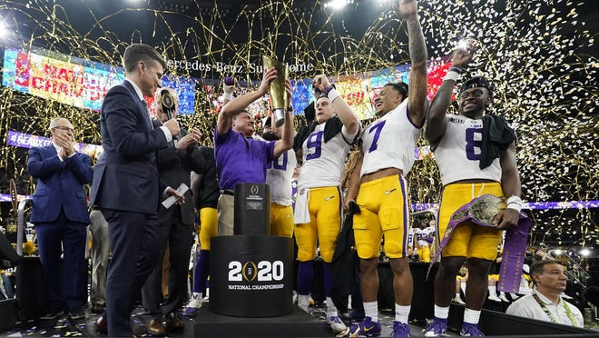 FILE - In this Jan. 13, 2020, file photo, LSU head coach Ed Orgeron holds the trophy after the team's victory over Clemson in an NCAA College Football Playoff national championship game in New Orleans. LSU has begun asking a number of football players to self-quarantine in the past week because of instances in which some players tested positive for COVID-19 after social interactions outside of the Tigers' training facility.