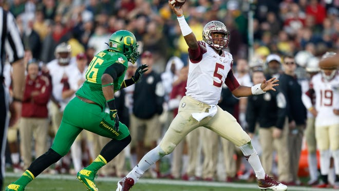 FSU's Jameis Winston throws the ball as he eludes pressure from Oregon's Christian French