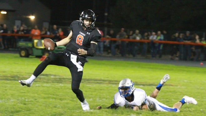 Grinnell quarterback Seth Howard, 8, gets out of the grasp of Bondurant-Farrar's Dalton Meyer, 11, during the Tigers' 24-17 loss on Friday in Grinnell.