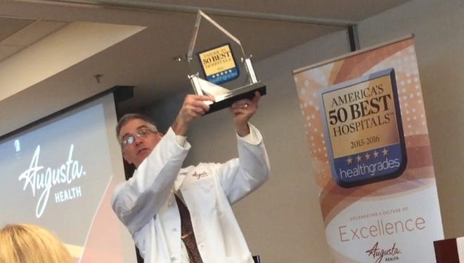 Augusta Health physician, Joe Ranzini, hefts the 2016 Healthgrades award for America's 50 best hospitals over his head following the award's presentation on Thursday.