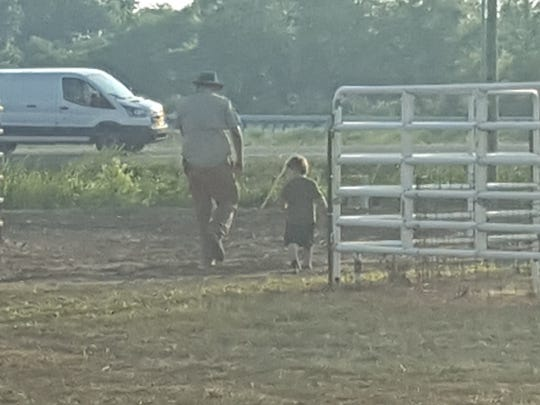 Jonathan Eblen strolls the Henderson County Fairgrounds with a young visitor during a lull in his volunteer duties.