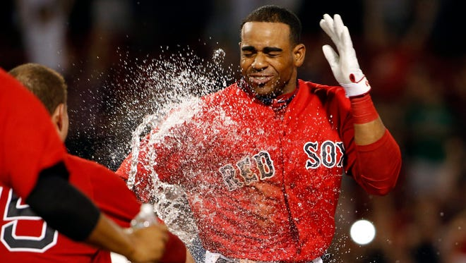 Boston Red Sox outfielder Yoenis Cespedes is doused by catcher Christian Vazquez after hitting the game-winning RBI single against the Toronto Blue Jays on Sept. 5, 2014.