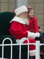 Santa and Tatum Kenyon, 4, smile for a photo at the
