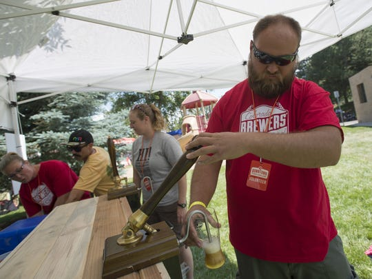 Tyler Mattson pours beer for McClellan's Brewing Company during the 2017 Colorado Brewers' Festival.