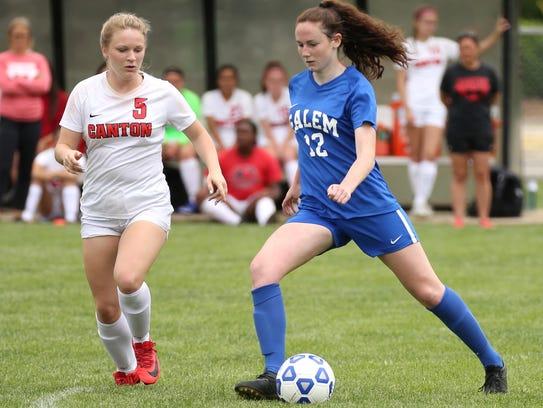 Salem senior forward Katie Coleman (12) dribbles past