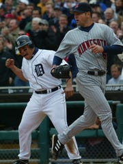 Pudge Rodriguez, left, celebrates a base hit by a teammate against the Twins on Opening Day at Comerica Park, April 8, 2004.