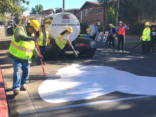 """Street crews apply a """"cool pavement"""" treatment on a residential street in the Canoga Park area of west Los Angeles. The city says the treatment lowers temperatures."""