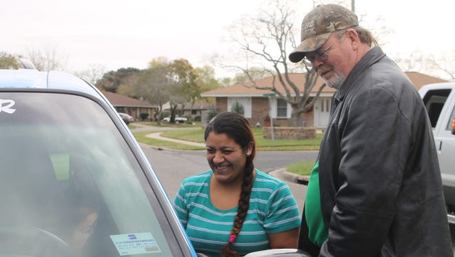 Sabrina Fonseca (left) smiles as Green N Go Cab Company owner Dan Stiefel shows her around her new car Friday, Dec. 30, 2016.