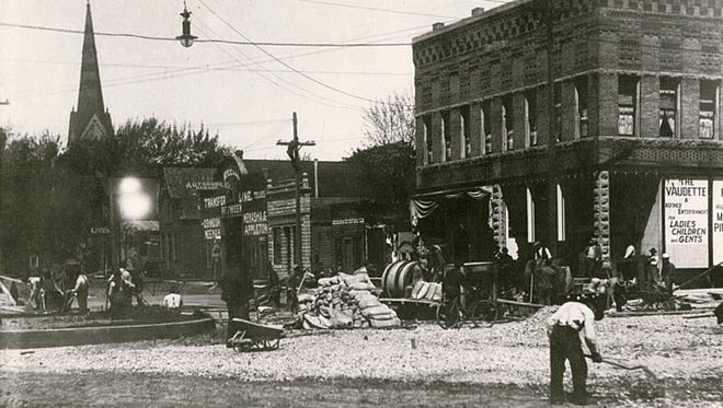 This 1910 photograph shows a view of the road construction at the corner of Main and Chute streets in Menasha. In the background is The Vaudette, Wheeler Transport and Trinity Lutheran Church.