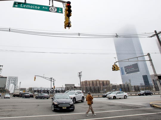 A pedestrians crosses the intersection of Lemoine Avenue and Bridge Plaza North in Fort Lee on Friday, April 21, 2017.