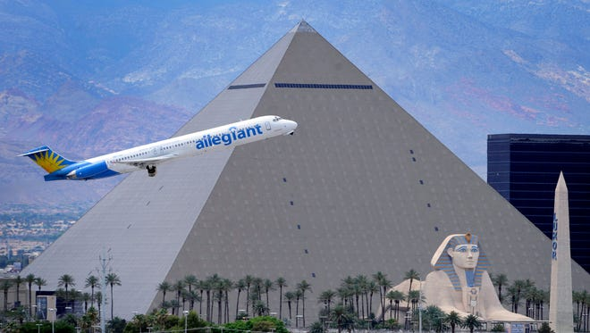 An Allegiant Air jetliner flies by the Luxor Resort & Casino after taking off from McCarran International Airport in Las Vegas.