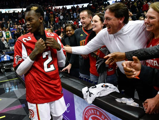 Atlanta Hawks guard Dennis Schroder, left, of Germany, puts on a Super Bowl-bound Atlanta Falcons' Matt Ryan jersey that fans gave him after an NBA basketball game against the Orlando Magic, Saturday, Feb. 4, 2017, in Atlanta.(AP Photo/John Amis)