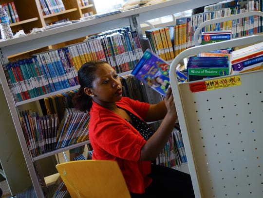 Shannon Pierce, a librarian assistant, helps shelve