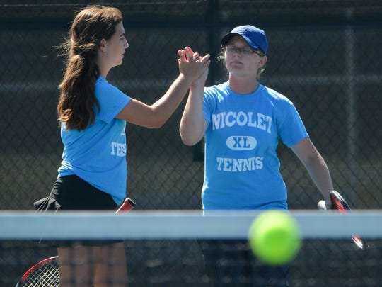 Nicolet No. 2 doubles players Marli Stellhorn (left) and Emma Koppa celebrate a point during their match against Neenah in the Nicolet Invitational girls tennis tournament Saturday.
