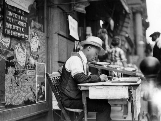 """The """"Treasures in Black and White"""" exhibit shows the bygone eras in Cincinnati history, such as this calligrapher scribing """"visiting cards"""" on the street while you wait in the early 1900s."""