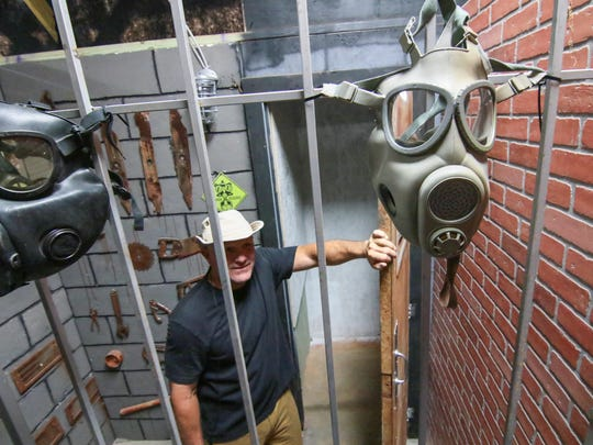 Ron Smith of Denver Downs stands behind gas masks and