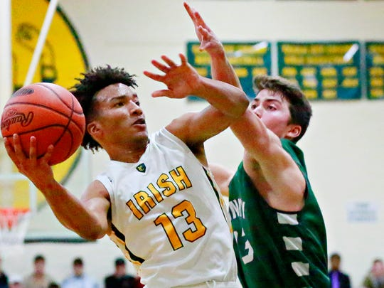 York Catholic's D'Andre Davis, left, takes the ball to the basket while Trinity's Matt Long defends during boys' basketball action at York Catholic High School in York City, Saturday, Dec. 9, 2017. Trinity would win the game 56-42. Dawn J. Sagert photo