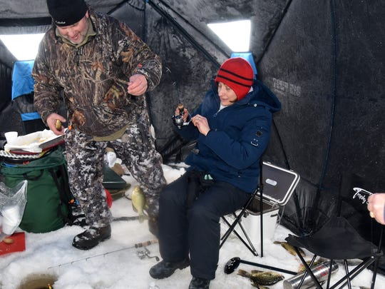 John Maier helps Penny Durkin land a crappie.