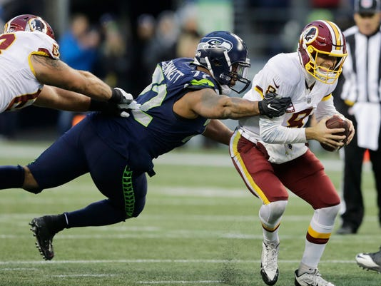 Washington Redskins quarterback Kirk Cousins, right, scrambles away from a tackle attempt by Seattle Seahawks defensive end Michael Bennett, left, in the second half of an NFL football game, Sunday, Nov. 5, 2017, in Seattle. (AP Photo/Stephen Brashear)