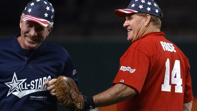 Pete Rose slaps hands with Hall of Famer Mike Schmidt during a celebrity softball game at Cinergy Field in 2002.