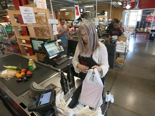 Amy Jerman cashes out the grocery order for an online