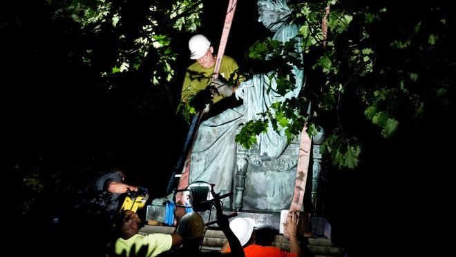 Workers remove a monument dedicated to U.S. Supreme Court Chief Justice Roger Brooke Taney from outside the Maryland State House, in Annapolis early Friday, Aug. 18. Maryland workers hauled several monuments away, days after a white nationalist rally in Charlottesville, Virginia, turned deadly.