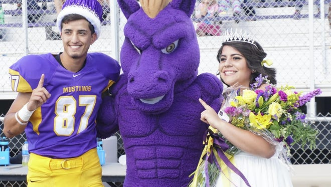WNMU Homecoming King Cavin Roberson and WNMU Homecoming Queen Alicia Soliz pose with Rawhide after being crowned.