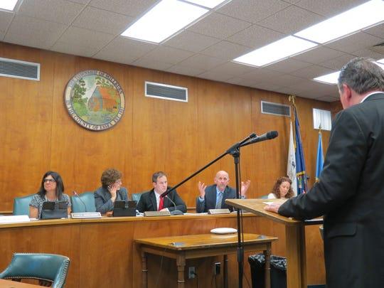 Township Committeeman Robert Tillotson, hands raised,