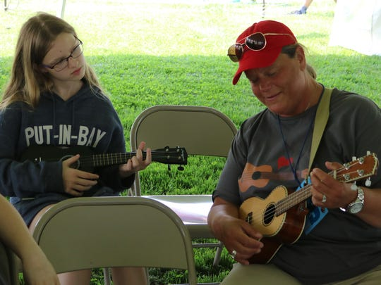 Sheryl Patry, right, gives a quick informal ukulele lesson to Taylor Cheves, 12, during the Put-in-Bay Music Festival.