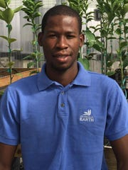 Jean-Yves Bérisse works in the UF greenhouse.