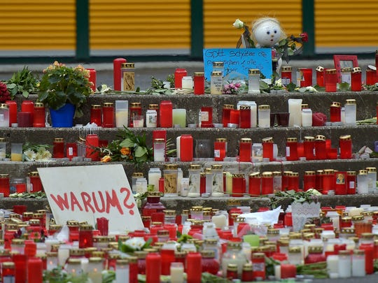 """Flowers and candles sit in front of the Joseph-Koenig Gymnasium in Haltern, Germany, Thursday. Sixteen students and two teachers from the school were among the 150 victims. The sign at left reads: """"Why?"""""""