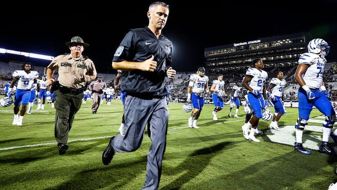 Dejected University of Memphis head coach Mike Norvell runs off the the field after falling to University of Central Florida 40-13 in Orlando, Fl., Saturday, September 30, 2017.