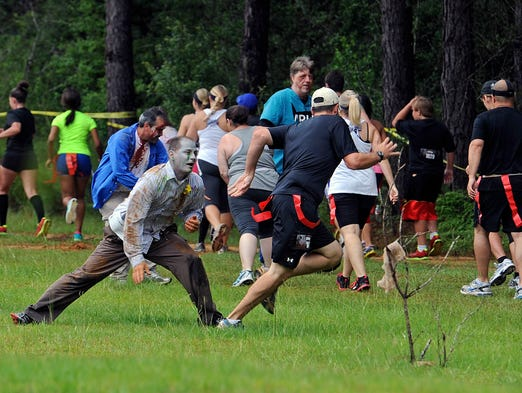 Zombies go after runners Saturday during the 2014 Zombie Run at the Escambia County Equestrian Center.