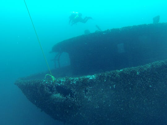Diver Greg Grieser swims by the stern of the Hydrus,