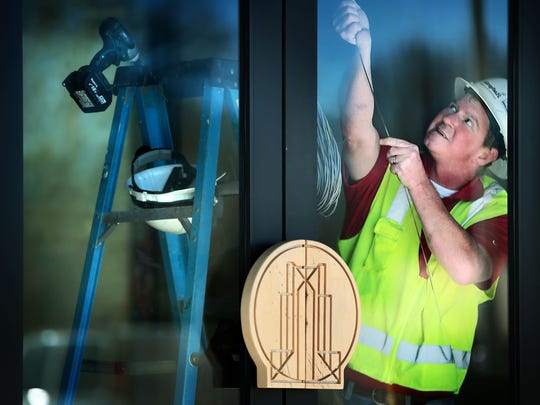 Jeramy Coppock installs wiring for the automated doors at the entrance to the main atrium at the Crosstown Concourse building where marketing firm Loaded For Bear has added little design touches like hand-carved maple door pulls.
