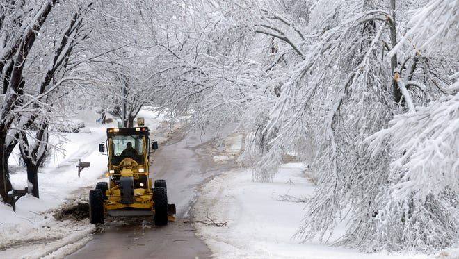 A grader clears snow after the Sioux Falls ice storm of 2013, which did heavy damage.
