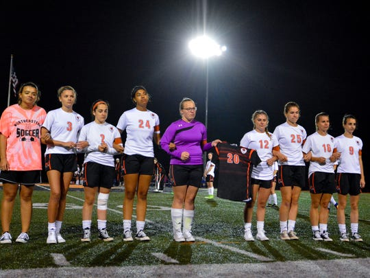 The Northeastern soccer team holds the jersey of senior Abby Osborn during a special tribute, Thursday, Oct. 12, 2017. Osborn was killed in a hit-and-run accident April 23. John A. Pavoncello photo