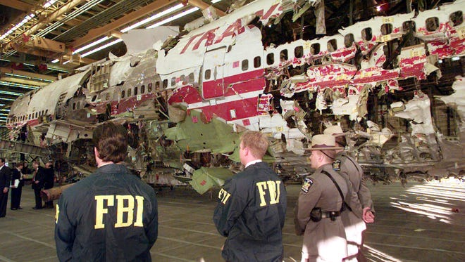 FILE - In this Nov. 19, 1997 file photo, FBI agents and New York state police guard the reconstruction of TWA Flight 800 in Calverton, N.Y. Flight 800 exploded and crashed July 17, 1996 while flying from New York to Paris, killing all 230 people aboard.