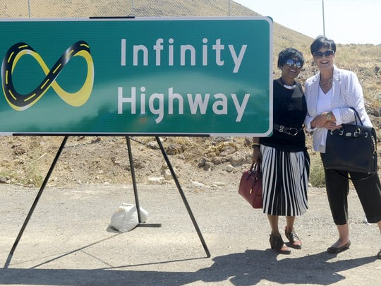 Praveen Ah Sam (left) and Kathy Flamm have their picture taken next to the new Infinity Highway sign revealed at the ceremony.