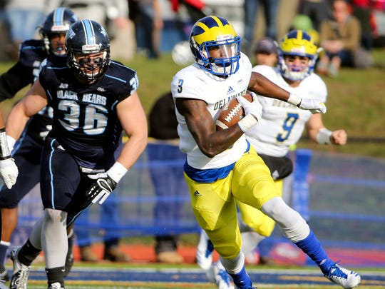 Delaware quarterback Joe Walker winds his way past the Maine defense, including Schuyler Huntington (left) on a second quarter scoring drive in the Hens' 31-17 win in Portland, Maine Saturday.