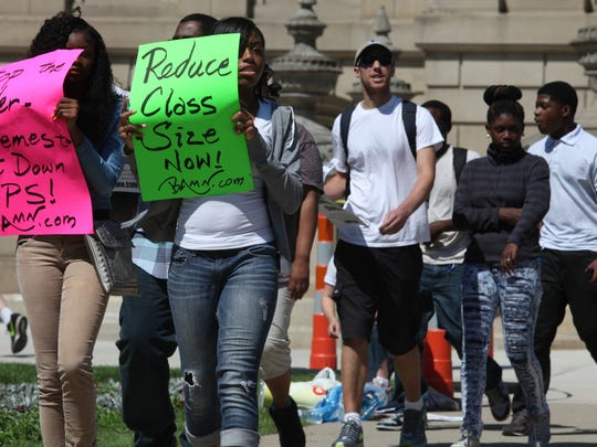 Alexa Dixon, 16, of Detroit and a junior at Detroit Northwestern High School marches with others to protest teacher health care changes and Governor Snyder's plan to reform education in Lansing today.